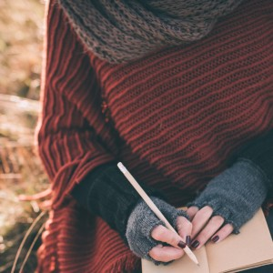Woman writing in notebook while seated outdoors