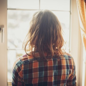 Woman looking out window at home