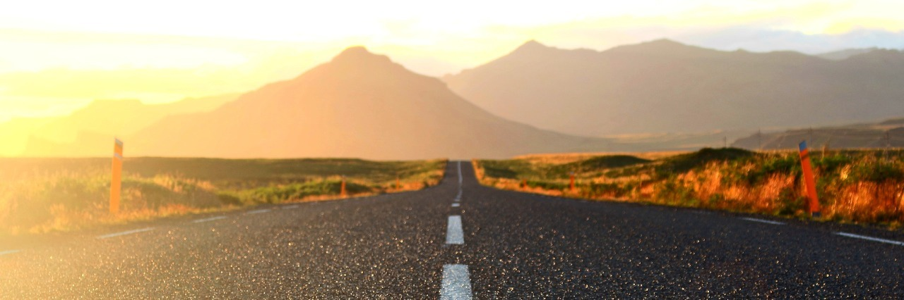 an open road leading to mountains