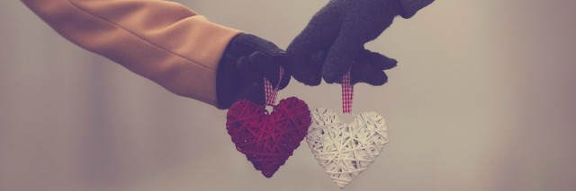 Two people wearing jackets and gloves, holding hearts toward each other