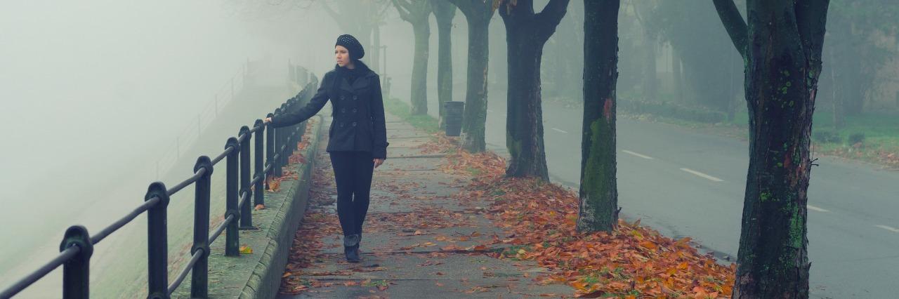 beautiful girl walking alone on misty autumn day