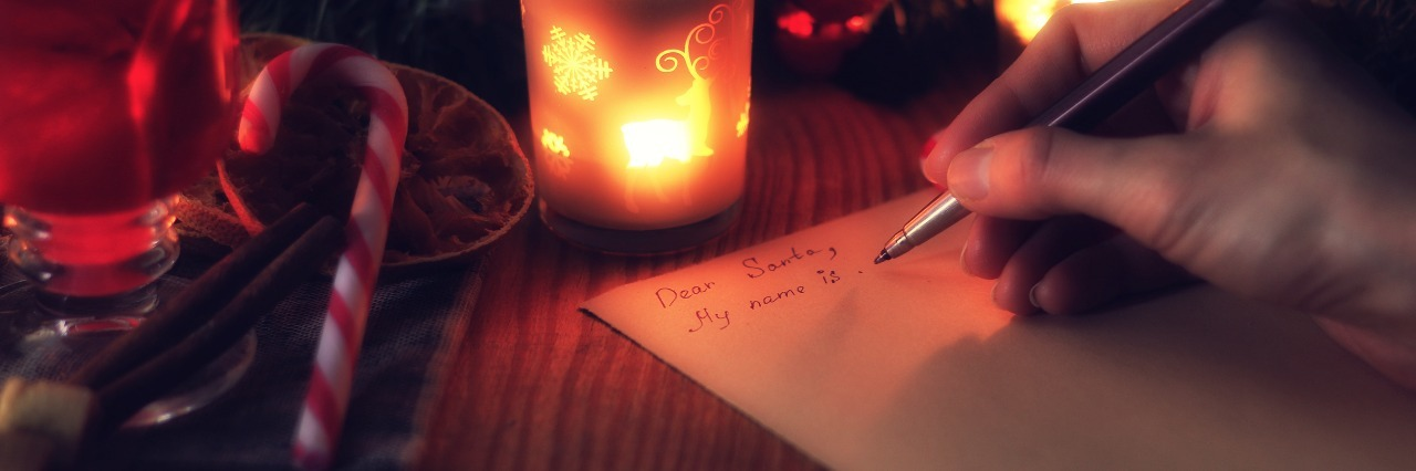 a person's hand writing their christmas wish list next to candles and a candy cane