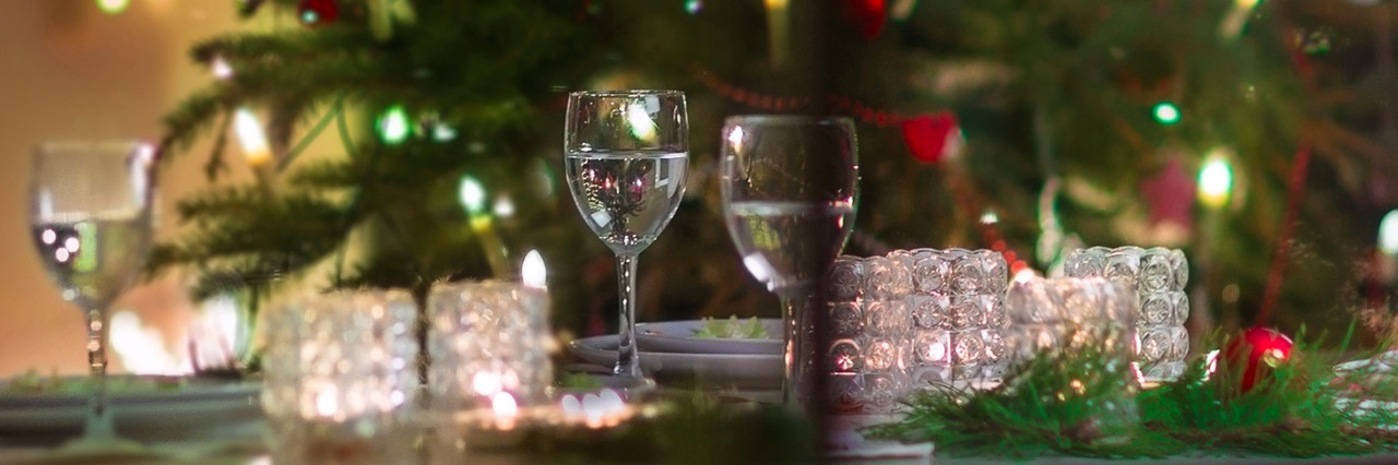 Christmas tree and table set with glasses from the perspective of outside the window