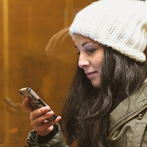Young adult female spends time with her smartphone on bus