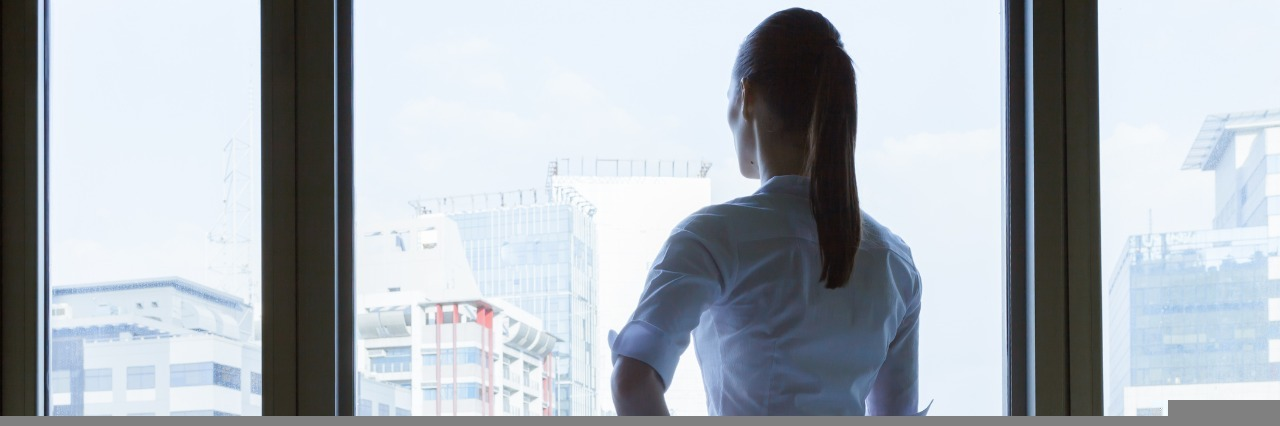 businesswoman stands alone in a conference room and looks out the window