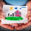 Child and his mom holding a drawn house with family