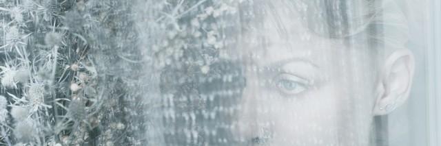 Woman face behind transparent cloth