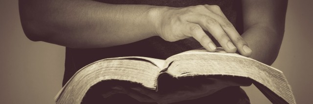 close up of man holding a bible in his hands and turning the page