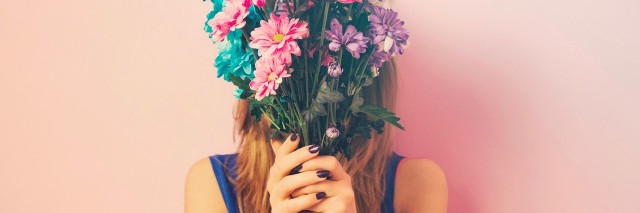 woman holding a bouquet of flowers in front of her face