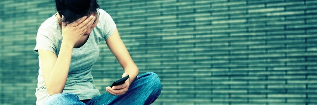 woman sitting on ground looking at cell phone