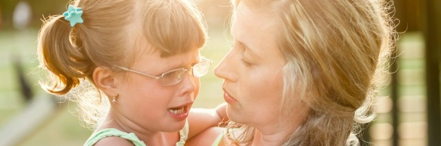 mother comforts crying daughter outdoors
