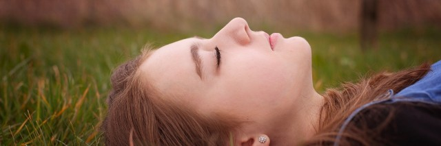 teenage girl lying on grass with her eyes closed