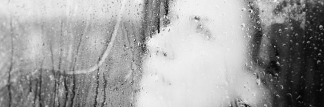 a womans face blurred through a window