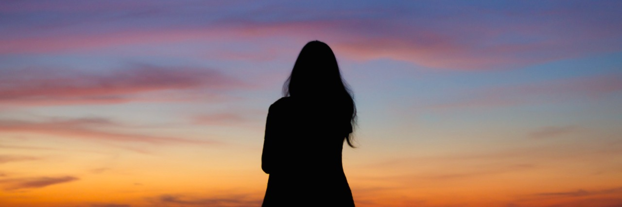 Silhouette of woman facing sky at sunset or sunrise
