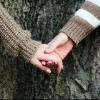 girls holding hands against tree bark in autumn