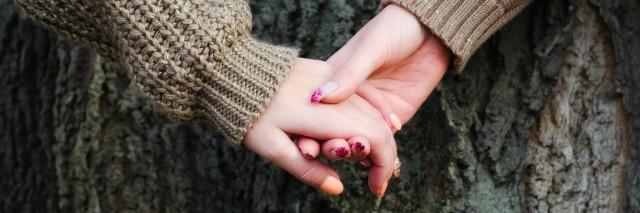 girls holding hands against tree bark in autumn