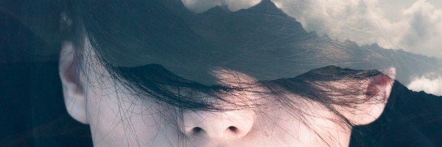 Double exposure portrait of young woman combined with photograph of mountainious landscape shot from a plane