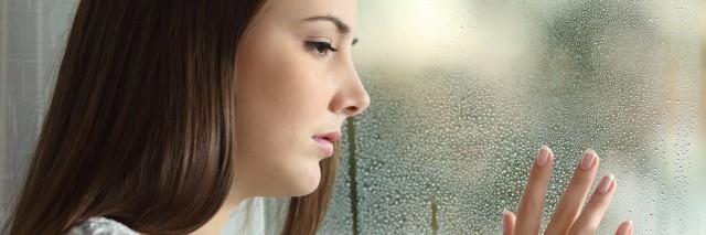 sad woman looking the rain falling through a window