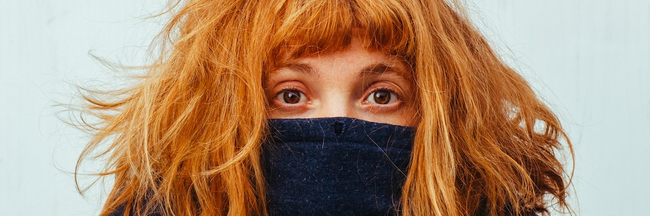 a woman hides behind her sweater