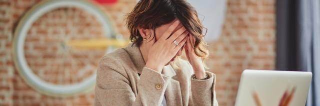 woman getting a Headache In Office