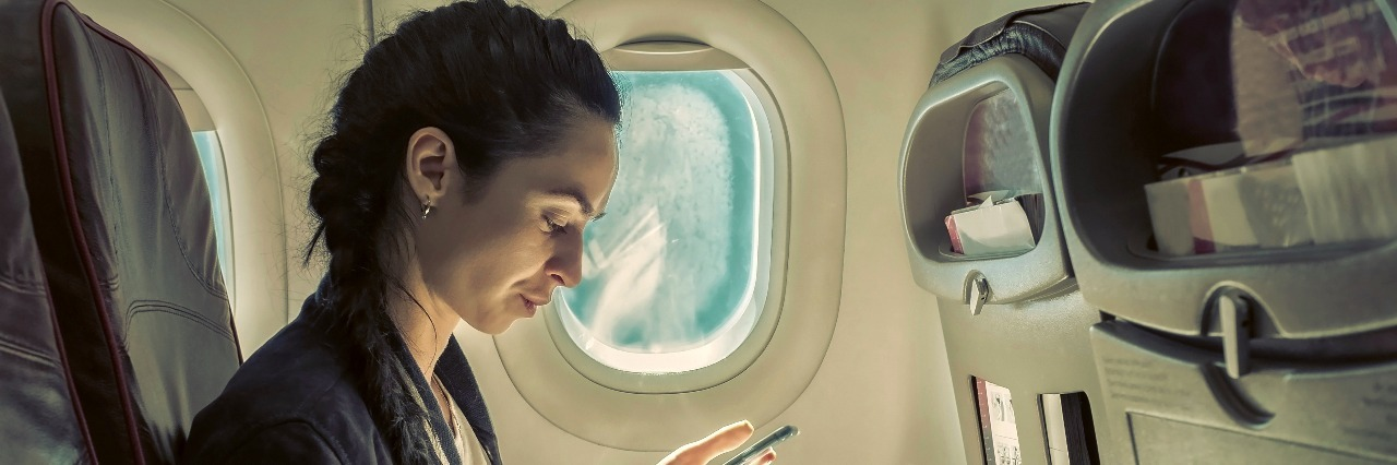 Woman sitting at airplane and looking at mobile phone.