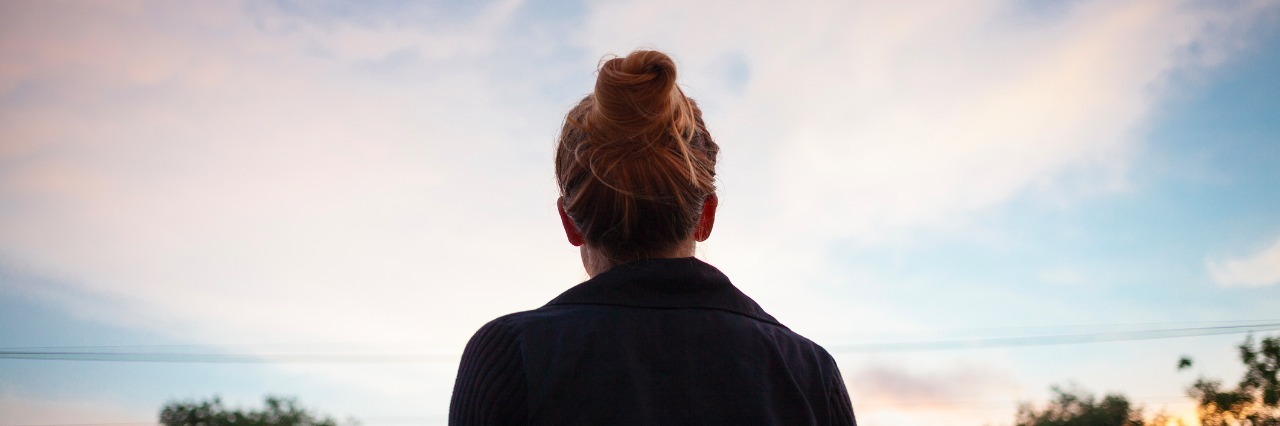 silhouette of a young woman looking at sunset