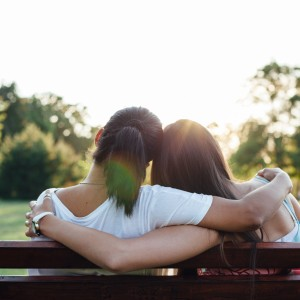 Closeup of mom and daughter embracing on a park bench