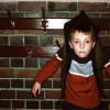 young boy attached to a coat hook by his jacket
