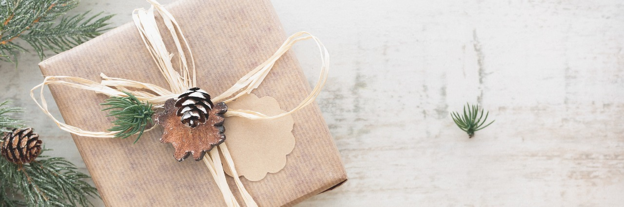 christmas gift wrapped in light brown paper next to christmas tree branches and acorns