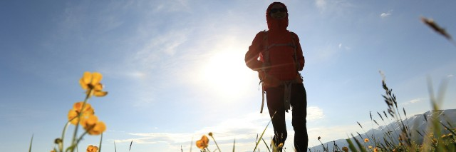 silhouette of young woman backpacker hiking on sunrise mountain peak