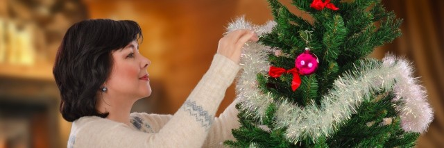 Middle-aged woman decorating Christmas tree with tinsels
