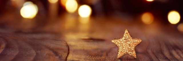 Holiday lights in background with gold glittering star on wood table