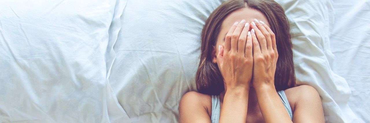 a girl laying in bed covering her face with her hands