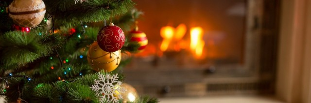 closeup image of golden baubles on Christmas tree at fireplace