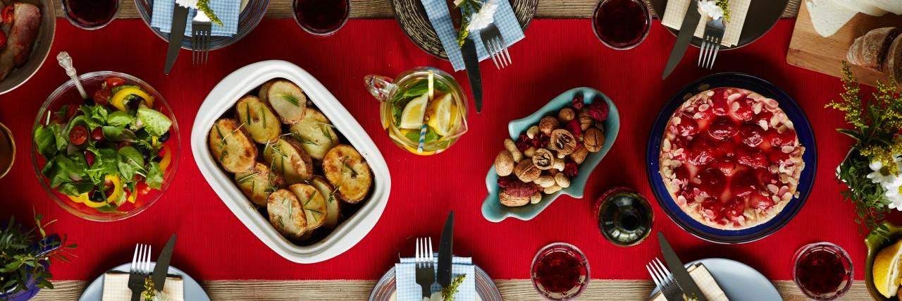 Baked potatoes, strawberry cake, homemade lemonade, vegetable salad, nuts and tableware prepared for dinner