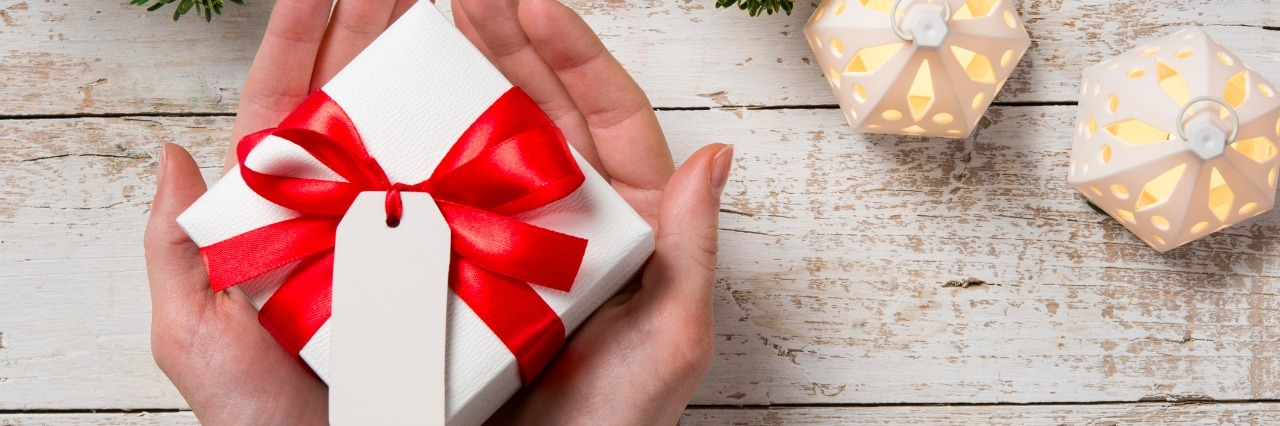 Top view of female hand holding white christmas gift box wrapped with red ribbon. High angle view of woman showing xmas present on rustic wooden table with fir branch on top.