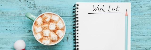 mug of hot cocoa and marshmallows, santa cap, and notebook with wish list on a blue table
