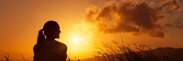 Woman watches the beautiful sunset/sunrise.