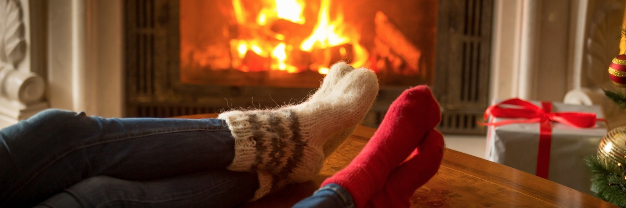 a couple wearing festive woolen socks relaxes in front of the fireplace and their christmas stockings