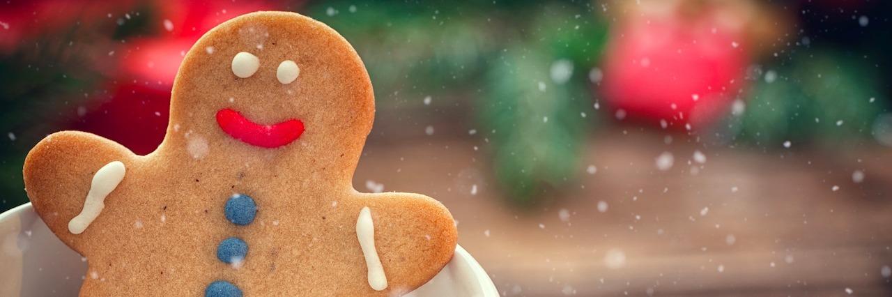 a gingerbread man sitting in a holiday mug
