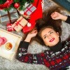 Young cute happy girl in sweater with deer lying on