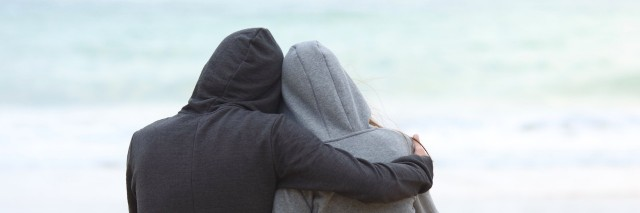 Two people wearing hoodies, hugging while facing the ocean on the beach