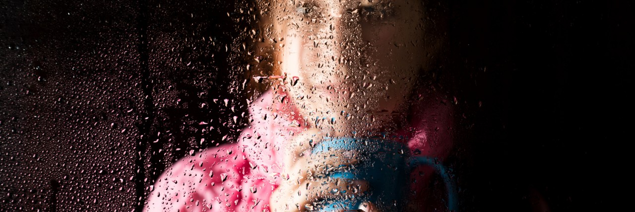 young sad woman portrait behind the window in the rain