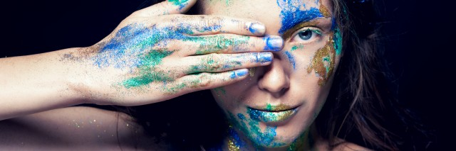 Beautiful face with colored paint on a black background