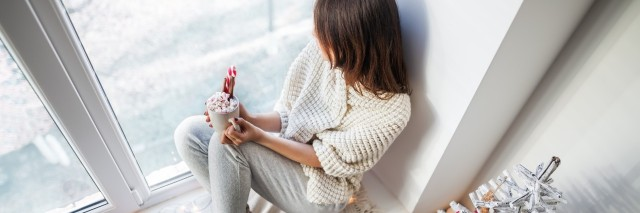 woman dressed in white sitting on a windowsill holding a cup of hot chocolate and looking at the snow