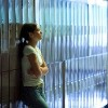 teenage girl leaning against lockers with her arms crossed at high school