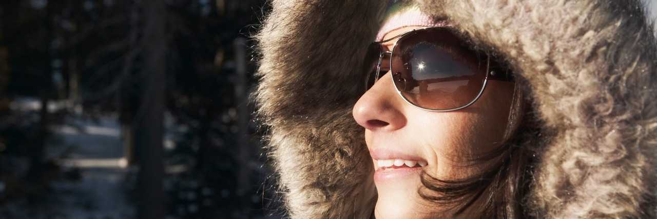 woman wearing heavy coat with fur hood and sunglasses and standing outside in the snow