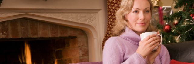 woman in purple sweater holding a mug and sitting by the fireplace and a christmas tree