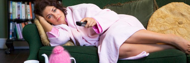 Young woman lying on sofa at home watching television