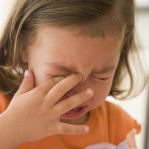 young girl crying and rubbing her eye